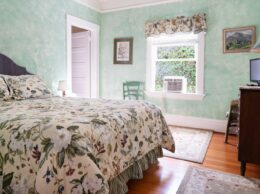 a floral bed rests in a green room