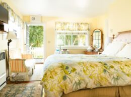 A yellow room hosts a floral bed, vanity, sunny window, and tv.