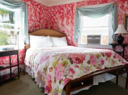 A large bed resrts in a pink and white room with a floral duvet and side tables.