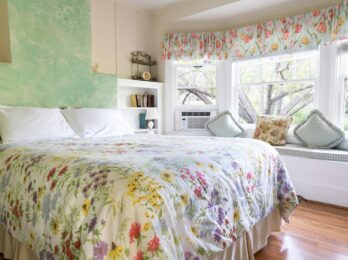 A bright and sunny room hold a bed with a wildflower duvet, green walls, a seating area in a bay window, book case, and floral curtains.